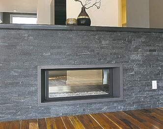 A two-sided, ribbon-style gas fireplace set in  grey stone adds style to the family room.