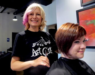 Mary-Lynne Kenneth (left) gives Melissa Hollinf a quick trim at Looks Hair and Body on Corydon Avenue. Kenneth has organized ArtCity Wednesdays. Every first Wednesday of the month she will be giving $25 basic haircuts with all proceeds going to ArtCity.