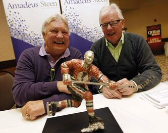 Bobby Hull and Ulf Nilsson at Canad Inns Polo Park on Friday, along with a miniature statue of the Golden Jet, which will be up for auction.