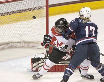 Team USA's Jocelyne Lamoureux (right) scores in the second period to give USA a 4-1 lead as Team Canada's Lauriane Rougeau looks behind her.