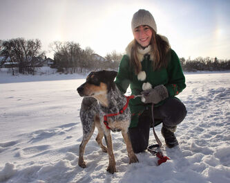 Vanessa Kuzina, with her dog Lucy, revisits the spot where she fell through the ice Friday.