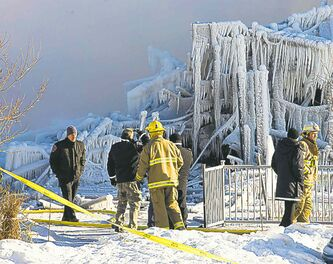 Investigators and firefighters look over the now frozen rubble.