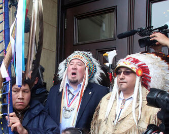 Derek Nepinak (centre), Grand Chief of the Assembly of Manitoba Chiefs, addresses protesters outside Parliament.