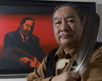 Elijah Harper holds one of two eagle feathers he raised during the Meech Lake debate in the Manitoba legislature.