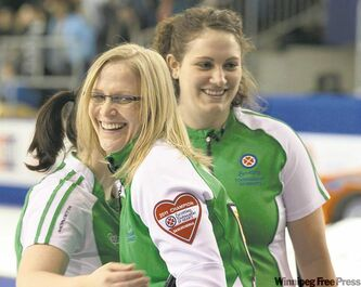 Saskatchewan skip Amber Holland is congratulated by second Tammy Schneider (right) and lead Heather Kalenchuk (left) after defeating Ontario in the semifinal. She faces a formidable challenge against three-time champ Jennifer Jones in today's final.