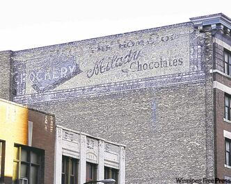 A 1906 crockery ad emerges from behind a later sign advertising chocolates.