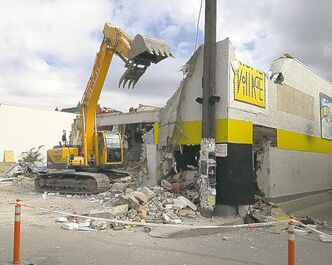 Crews demolish the old Movie Village building on Osborne Monday.