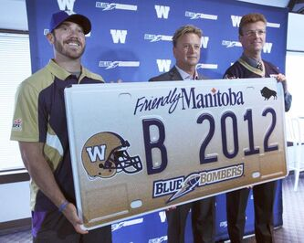 Winnipeg Blue Bomber QB Buck Pierce, Bomber President and CEO Garth Buchko and Justice Minister Andrew Swan unveil second-generation Winnipeg Blue Bomber plates in 2012.