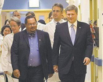 Arthur Porter (left) walks with Prime Minister Stephen Harper at the Montreal General  hospital in 2006. He now lives in the Bahamas.
