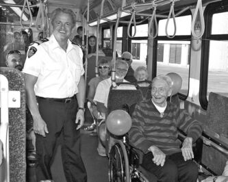 Fred Petruga enjoys a special ride with family and Winnipeg Transit's chief inspector George Fatouros (standing).