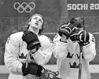 Sweden's Carl Hegelin and Erik Karlsson are dejected after losing 3-0 to Canada in the men's hockey gold-medal game at the Sochi Winter Olympics on Sunday.