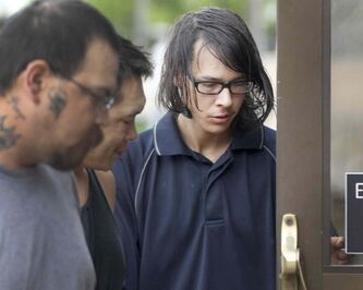 Jason Conway, 21, of MacGregor, Man., (right) is led into the provincial court house Monday in Portage la Prairie. He has been charged with first-degree murder in connection with the death of 96-year-old Niels