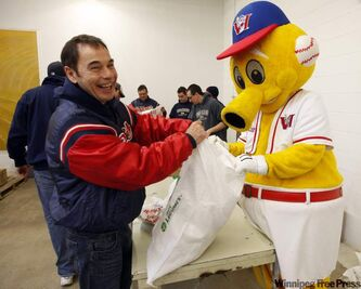 Goldeyes box-office manager Kevin Arnst (left) helps team masco Goldie pack food for Winnipeg Harvest.