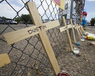 Crosses with the names of the deceased lean on a fence outside Fire Station 7 in Prescott, Ariz. on Tuesday, July 2, 2013 in a makeshift memorial for the 19 Granite Mountain Hotshots who were killed by an out-of-control blaze near Yarnell, Ariz. on Sunday. (AP Photo/The Arizona Republic, Tom Tingle)