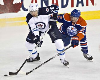 Winnipeg Jets' Blake Wheeler (26) battles for the puck with Edmonton Oilers' Jeff Petry (2) during first-period NHL hockey action in Edmonton Tuesday.