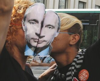 Demonstrators cover their faces with masks representing the Russian President Vladimir Putin and kiss during a demonstration in front of the Russian embassy in Paris.