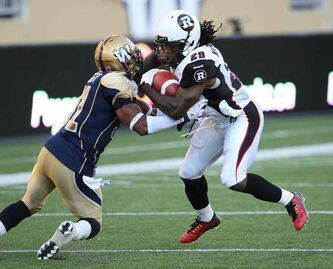 Winnipeg Blue Bombers Maurice Leggett ties it up with Ottawa Redblacks Chevon Walker during the first half of Thursday's game at Investors Group Field.