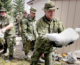 Pte. Jason MacFarlane (right) and fellow armed forces reservists help sandbag homes in Elie Wednesday.