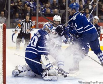Toronto Maple Leafs goaltender Jonas Gustavsson makes a save as Maple Leafs defenceman Cody Franson checks Winnipeg Jets centre Jim Slater (19) during first-period action in Toronto Thursday.
