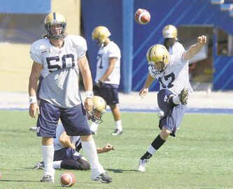 Justin Palardy drives into a snap from Chris Cvetkovic (50) during a Bombers pre-season workout at Canad Inns Stadium.