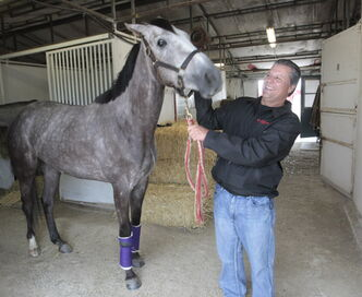 Kirt Contois, track announcer and Jockey agent with Katie Shimmers in the stables at Assiniboia Downs Thursday.