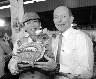Opposition Leader Tony Abbott poses with fruit art on the hustings. Australians vote Saturday.