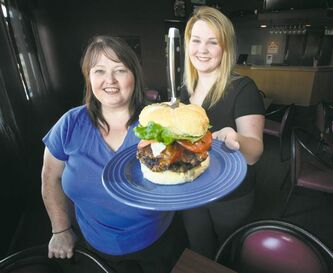 Jen (left) and her daughter Roxy, pose with an 'Xreme Dan,' a 20-ounce monster burger (served impaled on a steak knife) at Roxy's in Oak Bluff.