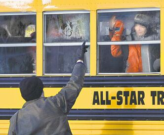 Jessica Hill / The Associated PressA man waves to a child on a bus on the first day of classes after the holiday break, in Newtown, Conn., Wednesday, nearly three weeks after the shootings.