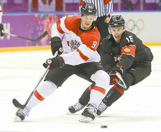 Austria's Oliver Setzinger (left) and Canada's Jonathan Toews chase the rubber Friday.