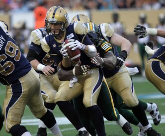 Winnipeg Blue Bombers' quarterback Drew Willy gets wrapped up in the arms of Edmonton Eskimos Almondo Sewell in the second quarter of Thursday's game at Investors Group Field.