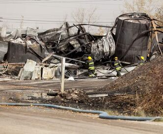 Firefighters put out hotspots at Speedway International the day after the blaze.