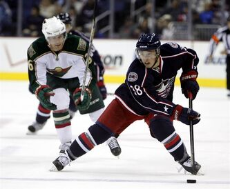 Columbus Blue Jackets' Cam Atkinson (38) looks to pass the puck as Minnesota Wild's Marco Scandella (6) gives chase during the second period of an NHL preseason hockey game on Thursday, Sept 29, 2011, in Columbus, Ohio. The Blue Jackets won 4-2. (AP Photo/Terry Gilliam)