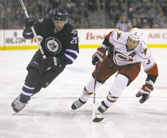 Winnipeg Jets� Blake Wheeler (26) and  Carolina Hurricanes� Tim Gleason (6) race to the puck during second period hockey action at MTS Centre in Winnipeg, Saturday, March 30, 2013. (TREVOR HAGAN/WINNIPEG FREE PRESS)