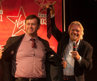 Sir Richard Branson holds up the end of a tie he cut from Rob Farina, Executive Vice President of Content at Astral Radio, during Branson's Winnipeg Chamber of Commerce Q&A at the Fairmont Hotel on Friday.