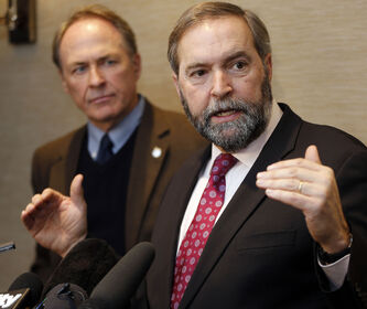 Official Opposition leader Tom Mulcair, right, stopped at the Fairmont Winnipeg on the second day of the NDP's 'affordability tour; where he took aim at ATM fees and oil companies. Also with him was MP Pat Martin.