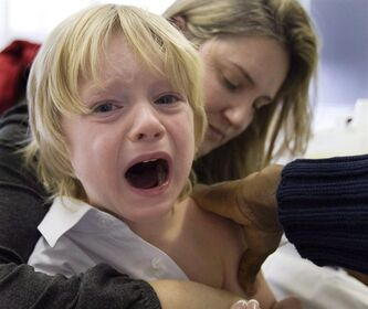 Evan Tordorf, 4, cries as he gets his flu shot as his mother and Karen Joly looks on at a H1N1 vaccination centre in 2009 in Montreal. (Canadian Press archives / Ryan Remiorz)