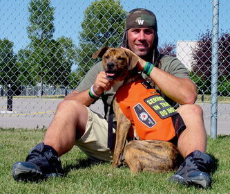 Winnipeg Blue Bomber Chris Cvetkovic with Lobo, a 9-month-old boxer-mix from Bonfil, Mexico. Cvetkovic is training Lobo to be a service dog for a Canadian Armed Forces personnel suffering from PTSD as part of Cvet's Pets work with Manitoba Search and Rescue's Courageous Companions program.