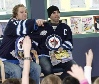 Jets Andrew Ladd (right) and Bryan Little visit Riverbend Community School to read books and sign autographs on Monday.