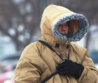 A pedestrian is prepared for high winds and snow on Notre Dame Avenue and Balmoral Street Friday afternoon.