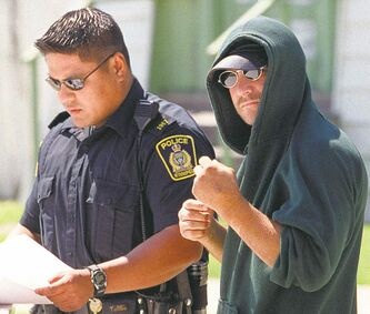 Kevin Sylvester shoots a hostile gesture at a photographer as police interview him in July 2001 outside his house.