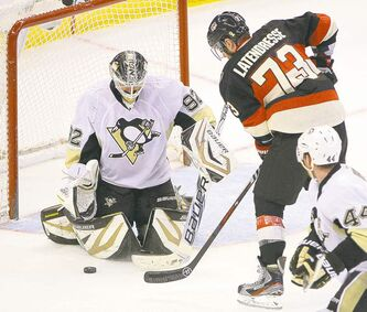 Penguins' goalie Tomas Vokoun eyes the puck as Senators' Guillaume Latendresse fights for possession. Pens took the teams' regular-season meetings 3-0.