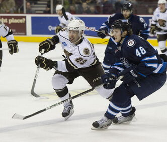 Hershey Bears' Juilien Brouillette (29) and St. John's Icecaps' Carl Klingberg (48) race for the puck last month. The IceCaps' head coach says Klingberg has good skills and is working on consistency.