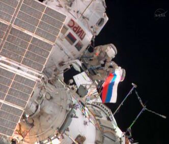 In this image from video made available by NASA, cosmonauts Fyodor Yurchikhin, left, and Aleksandr Misurkin wave a Russian flag near the end of their spacewalk outside the International Space Station on Thursday, Aug. 22, 2013. (AP Photo/NASA)