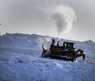 A bulldozer works today at the city's McPhillips Street and Rossmore Road snow dump.