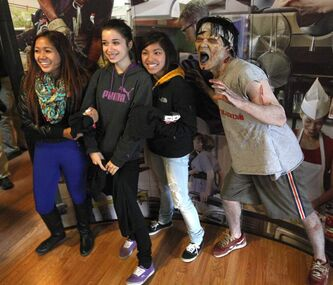 Tec Voc High students, from left, Allison Nanucl,  Diana Rodriguez , and Airiana Gonzales get their photo taken with zombie actor Brian Kawakami who was in attendance Tuesday to launch Safe Work Manitoba's youth campaign called Spot the Zombie Manitoba.