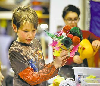 Robert Montgomery, 9, works on a Christmas-themed puppet.