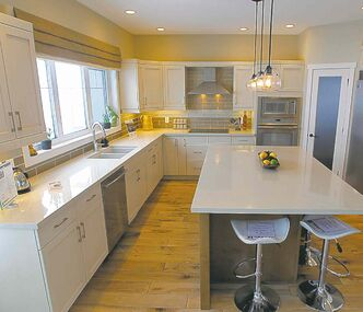 The kitchen features light-stained maple cabinets, earth-tone quartz countertops and taupe/tan glass.
