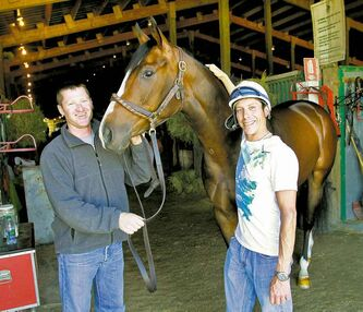 Trainer Chad Torevell (left) and jockey Robert Reeves Jr. with She's Regal in the stable area at Assiniboia Downs.