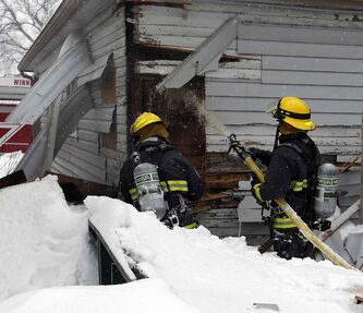 Firefighters cut into rear walls of a house on Union Avenue West near Roch Street.