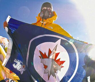 Dean Carriere on top of Mount Everest holding a Winnipeg Jets flag.